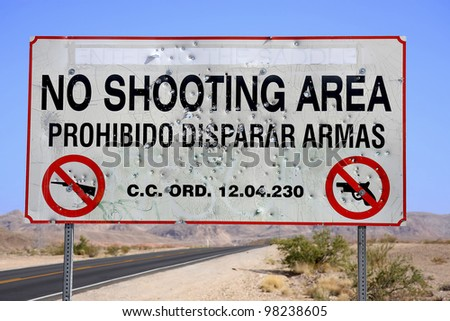 warning sign no shooting with bullet holes and graffiti