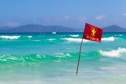 Warning sign of a red flag at a beautiful beach with a blue sky and a turquoise sea. Do Forte Beach in Cabo Frio, Rio de Janeiro, Brazil.