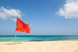 warning sign of a red flag at a beautiful beach with a blue sky and a turquoise sea, Fuerteventura, Canary Islands, Spain, Europe