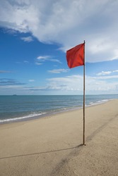 warning sign of a red flag at a beautiful clean beach with a blue sky, cloud and the sea, High contrast ans colorful picture style