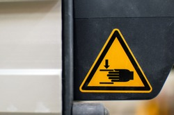Warning sign on agricultural machinery. Do not put your hands out. Injury to hands is possible.