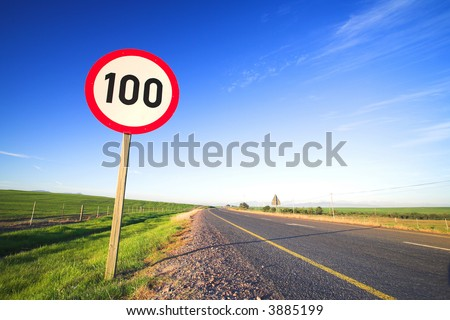 Warning sign or road sign for the maximum speed limit next to an empty road on a sunny summer day. Focus on the numbers ? saturated colors (polarized image) #3885199