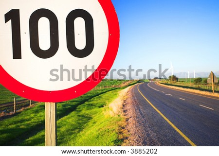 Warning sign or road sign for the maximum speed limit next to an empty road on a sunny summer day. Focus on the numbers ? saturated colors (polarized image) #3885202
