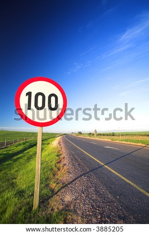 Warning sign or road sign for the maximum speed limit next to an empty road on a sunny summer day. Focus on the numbers ? saturated colors (polarized image) #3885205