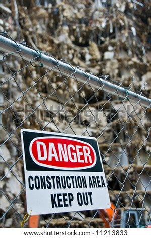 warning sign posted on fence around massive demolition project, shallow depth of field - part of series