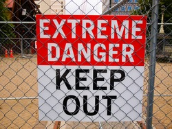 warning sign posted on the fence