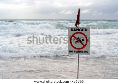 Warning sign with stormy ocean behind.