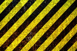 Warning sign yellow and black stripes painted over rusty metal plate as texture background. Concept for do not enter the area, caution, danger, hazard.