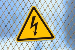 warning sign, yellow triangle with lightning on a fence made of metal mesh.