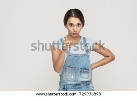 Warning sign. Young adult middle eastern woman, looking at camera with serious face and finger warning. Studio shot. Gray background.