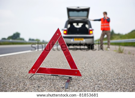 Warning triangle behind a broken down car with a motorist calling for assistance. Focus on the triangle