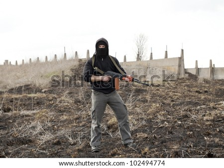 Warrior with gun in the battlefield