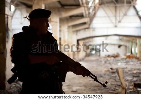 Warrior with Kalashnikov machine gun on the ruined building background.