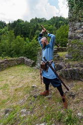 warrior with thick beard brandishes an ax, an image of historical re-enactment among the medieval ruins