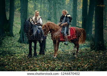 Warriors Woman an Man on horses in the woods. Scandinavian vikings riding horse with axes in hands. Traditional clothes with fur collar. Reconstruction of a medieval scene