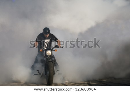 WARSAW - AUGUST 29: Biker burning tire and creating smoke. American Day in Warsaw on August 29, 2015 in Poland