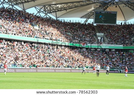 WARSAW - AUGUST 7 : Football fans in Legia Warsaw New Stadium watch a friendly match between Legia Warsaw and Arsenal London on August 7, 2010 in Warsaw, Poland.