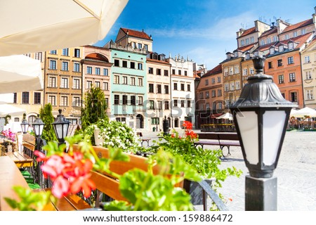 Warsaw old town marketplace square, street lamp in cafe and flowers on foreground Zdjęcia stock ©