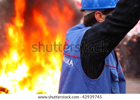 WARSAW, POLAND - DECEMBER 15:  Closeup of Solidarity protester with burning tires in the background during anti government Solidarity demonstration on December 15, 2009 in Warsaw, Poland.