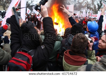 WARSAW, POLAND - DECEMBER 15: Photographers and burning tires during anti government Solidarity demonstration on December 15, 2009 in Warsaw, Poland.