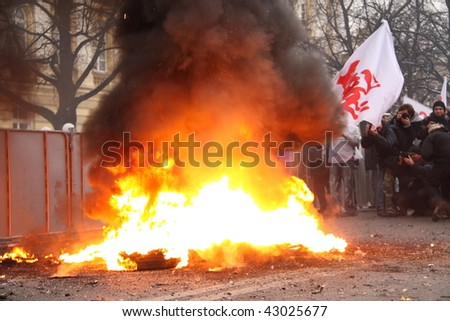 WARSAW, POLAND - DECEMBER 15: Protesters watch burning tires in the street during anti government Solidarity demonstration on December 15, 2009 in Warsaw, Poland.