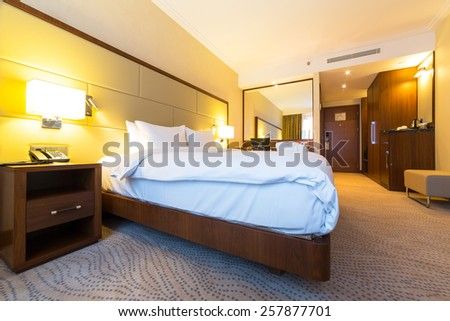 WARSAW, POLAND - 27 FEBRUARY 2014: Luxury bedroom of DoubleTree by Hilton Hotel & Conference Centre in Warsaw, Poland. DoubleTree by Hilton has over 400 hotels and resorts around the world.