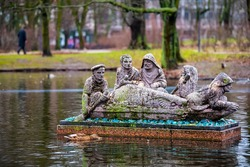 Warsaw, Poland Krasinski palace park garden in winter of Warszawa, waterfowl ducks birds swimming in pond lake by fishermen in boat stone statue on water