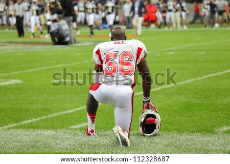 WARSAW, POLAND - SEPTEMBER 1: American football player, US team member Mike Gee (DL/LB) kneels down on the field before the game during Euro-American Challenge match on September 1, 2012 in Warsaw.