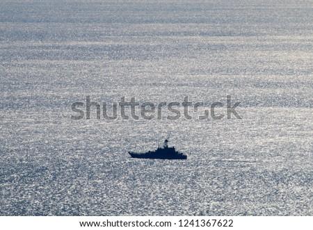 Warship, patrol vessel, coastguard in the Kerch Strait from the Black sea to the Azov sea. Beautiful silvery sea from a bird's-eye view Stock fotó ©