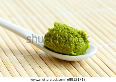 Wasabi paste on ceramic spoon on bamboo mat. Stock fotó ©