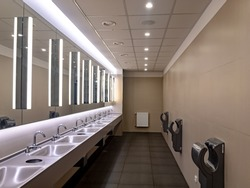 Wash-basins and hand dryers in a modern brown restroom with large mirrors