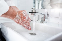 Wash hands thoroughly with soap and hot water. Protection against coronavirus through frequent hand washing. Background for a hygiene concept.