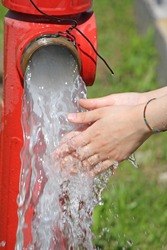 Wash hands under the powerful jet of water from a fire hydrant