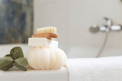 Washbasin in white bathroom with bath accessories. Hotel cleaning concept. Household concept. Washcloth, soap, foot brush, towel and eucalyptus branch with green leaves. High quality photo