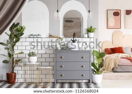 Washbasin on grey cabinet under mirror in open space interior with bed under posters. Real photo - Shutterstock ID 1126568024