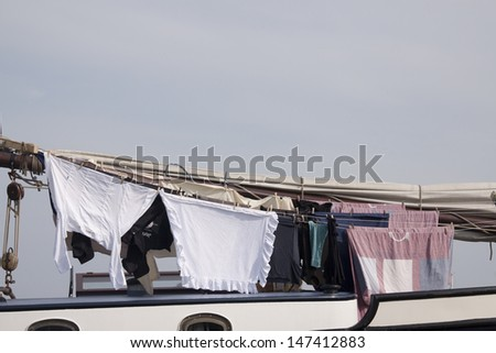 Washed clothes pieces hang to dry on board a boat