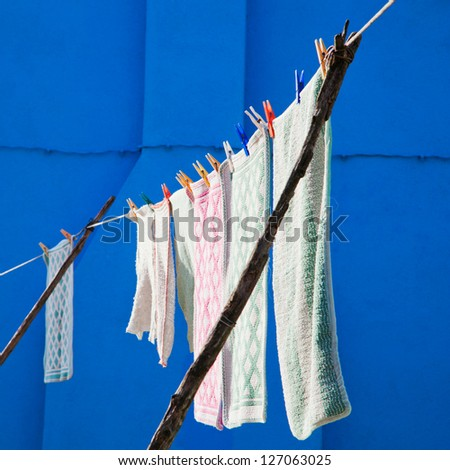 washed laundry hanging on a line to dry with a blue wall in the background, seen in Venice, Italy