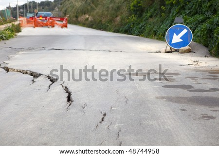 Washed out and damaged road with blue traffic sign pointing direction to attract attention
