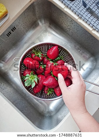 Washed ripe juicy red strawberries in mesh strainer above sink in kitchen, POV and top view Stock photo ©