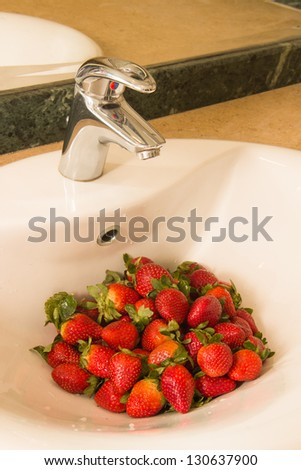 washed strawberry in white ceramic sink