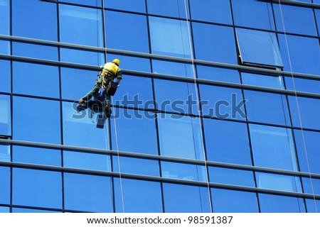 Washer wash the windows of modern skyscraper, high risk work - stock photo