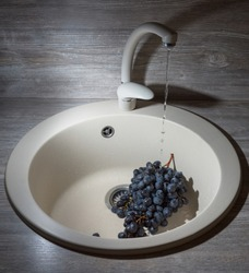 Washing a branch of grapes in the sink.