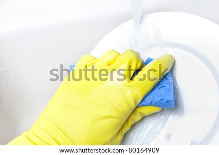 Washing a white plate with a sponge and rubber gloves