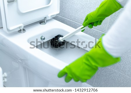 Washing and disinfecting toilet using cleaning scrub brush. Cleaning service and household chores #1432912706