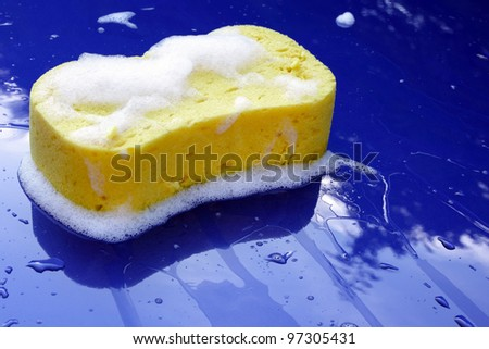 Washing bonnet of blue car with a sponge - stock photo