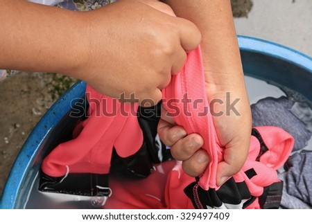 washing clothes by hand in plastic tubs #329497409