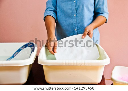 Washing dishes by hand to save water.