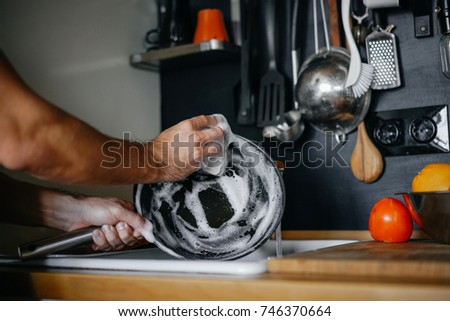 washing dishes. male hands in foam washes the frying pan with a detergent and sponge in the kitchen of the house.