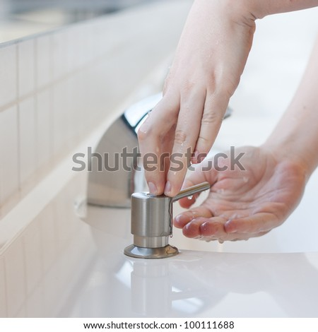 Washing hands in a public restroom - applying soap (selective focus)