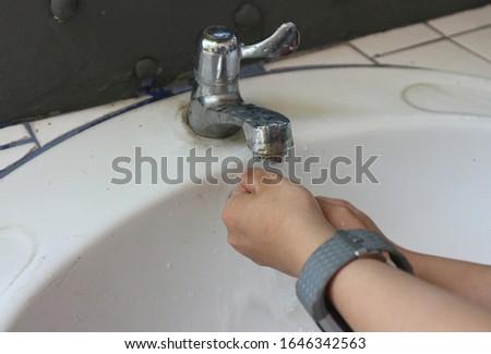 Washing hands under flowing tap water. Hygiene concept.